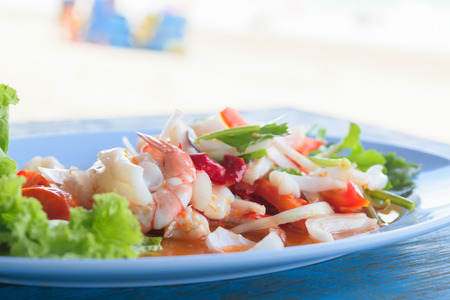 repast: Mixed seafood salad and fork in dish on blue wood table Stock Photo