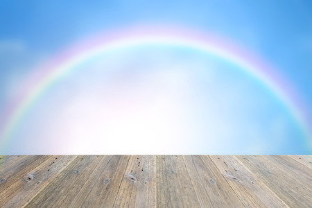 rainbow scene: Wood terrace and blurred Blue sky and white cloud with rainbow Stock Photo