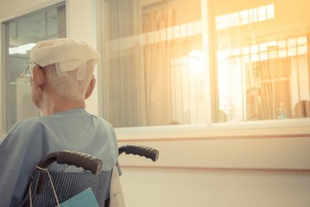 Patiënt oudere man met hoofdletsel op rolstoel in het ziekenhuis, Vintage stijl Stockfoto