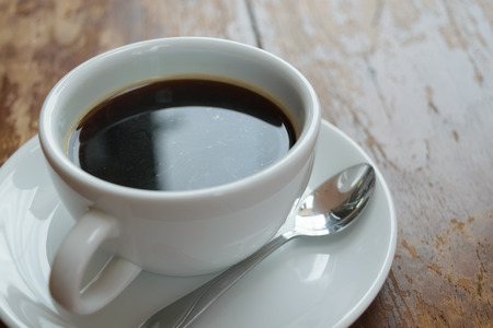 Koffie in witte kop op houten tafel Stockfoto