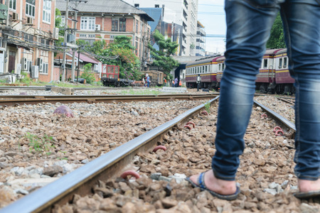 piernas: Man with jeans and slippers standing on railroad track