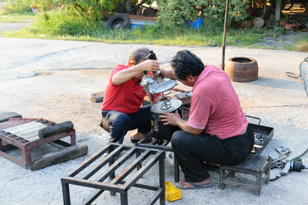 two car garage: Bangkok, Thailand - April 5, 2015 : Unidentified two workers repair car truck part at garage.