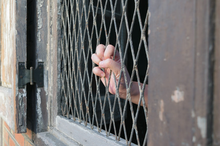 locked up in a cage: Hands of the man on a steel lattice close up Stock Photo