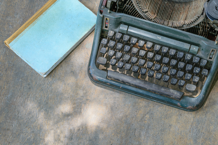 Vintage typewriter and a notebook on a wood table