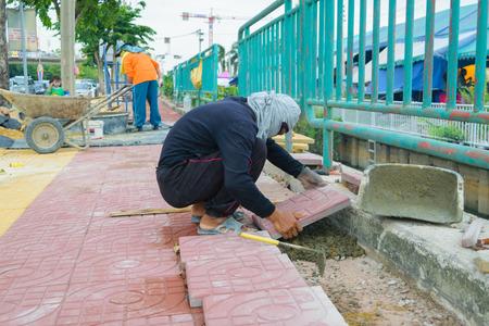 paver: Bangkok, Thailand - September 11, 2015 : Unidentified worker laying paver bricks paver making sidewalk