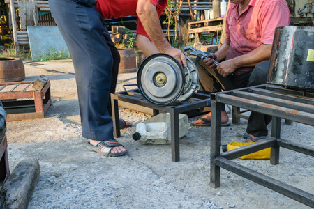mot: Bangkok, Thailand - April 5, 2015 : Unidentified two workers repair car truck part at garage.
