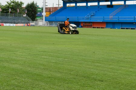 pat: Bangkok, Thailand - September 15, 2015 : Unidentified man mowing the grass on a football stadium at PAT Stadium. PAT Stadium is a stadium in the Khlong Toei district Bangkok, Thailand. Editorial