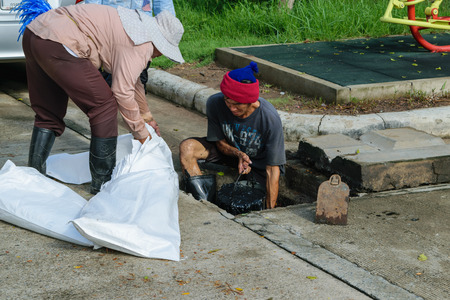 full of holes: Bangkok, Thailand - October 11, 2015 : Unidentified worker working for drain cleaning. Problem with the drainage system. Editorial