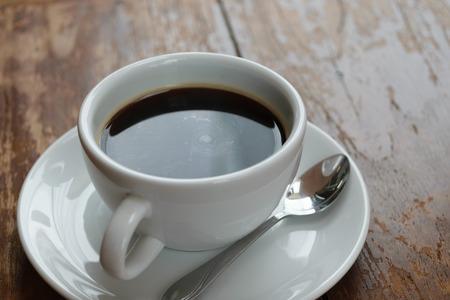 Koffie in witte kop op houten lijst