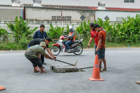 full of holes: Bangkok, Thailand - October 17, 2015 : Unidentified worker working for drain cleaning. Problem with the drainage system.