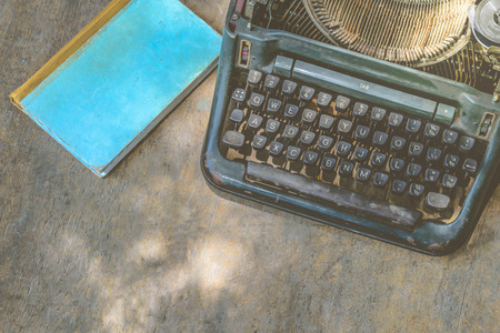 old desk: Vintage typewriter and a notebook on a wood table , process in vintage style Stock Photo
