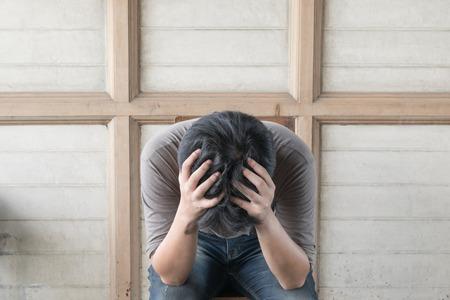 Ängstliche asiatischer Mann Gefühl Traurigkeit und Stress auf dem Stuhl sitzt
