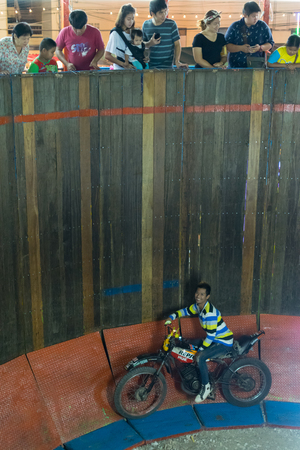 trial indoor: Bangkok, Thailand - January 9, 2016 : Unidentified asia rider motorcycle extreme show by climb and run on the circle wooden wall in a temple festival.