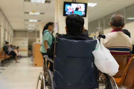 Patient elderly on wheelchair and many patient waiting a doctor and nurse in hospital