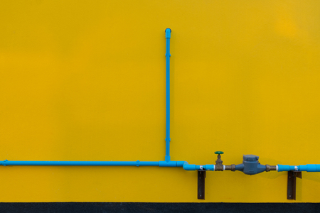 Minimalism style, Blue water pipe with faucet valve on yellow wall texture background.