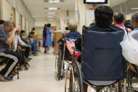 Paciente anciano en silla de ruedas y muchos pacientes en espera de un médico y una enfermera en el hospital