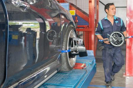 disassembly: Bangkok, Thailand - January 16, 2016 : Unidentified serviceman checking suspension in a car at garage