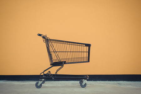 Minimalism style, Shopping cart black color and yellow wall at supermarket. , process in vintage style Stock Photo
