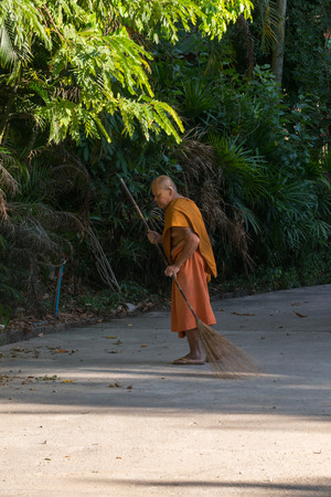 thai monk: Chanthaburi, Thailand - February 1, 2016 : Thai monk sweeping a temple floor for clean at Thai forest temple (Wat Pa) in the Na Yai Am District of Chanthaburi, Thailand. Editorial
