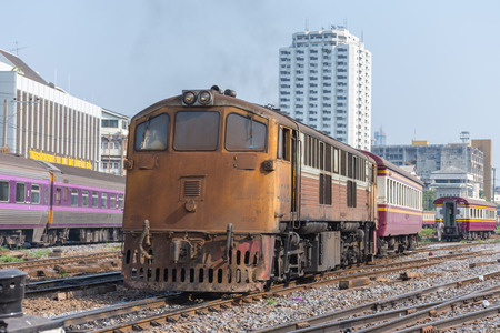 cheaper: Bangkok, Thailand - April 26, 2016 : Unidentified railway train on the railroad tracks in Bangkok station. Many people in Thailand popular travel by train because it is cheaper.