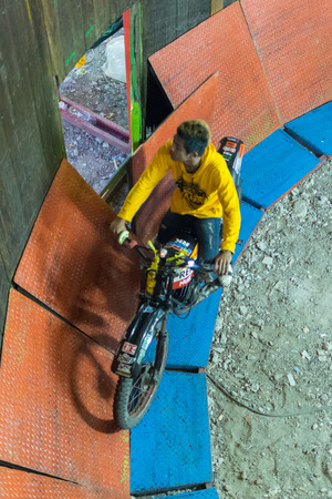 trial indoor: Bangkok, Thailand - January 10, 2016 : Unidentified asia rider motorcycle extreme show by climb and run on the circle wooden wall in a temple festival.