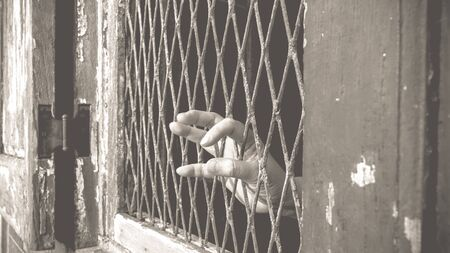 incarcerated: Hands of the anxious woman on a steel lattice close up , process in vintage black and white style.