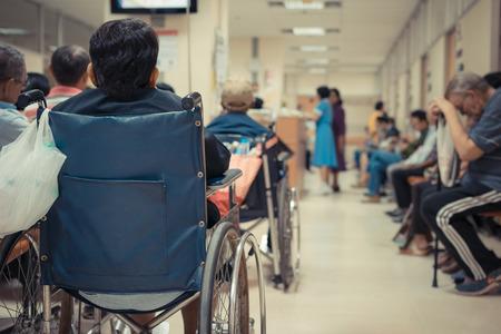 Patiënt ouderen op rolstoel en vele patiënt wachten op een arts en verpleegkundige in het ziekenhuis