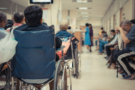 asian hospital: Patient elderly on wheelchair and many patient waiting a doctor and nurse in hospital