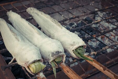 snakehead: Salt-Crusted Grilled Snakehead fish grill on charcoal stove at market , process in vintage style