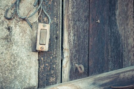 Minimalism style, Dirty doorbell (bell bottoms) on the old wall with wood texture background. , process in vintage style