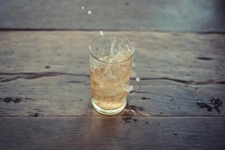 vasos de cerveza: La cerveza se extendió en vidrio con hielo y espuma en una mesa de madera, proceso en el estilo de la vendimia