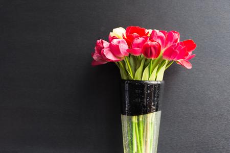 color in: tulipanes de color rojo hermoso de la flor en el florero negro sobre fondo negro Foto de archivo