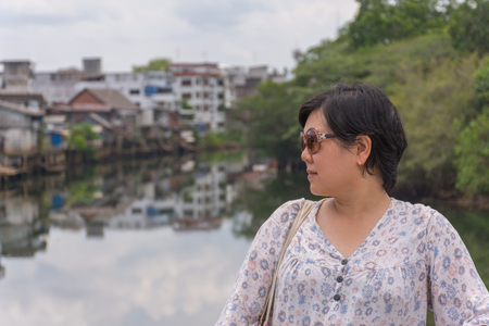 river side: Asia woman plump body with sunglasses standing at river side when travel