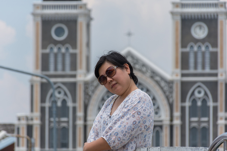 plump: Asia woman plump body with sunglasses standing at Roman Catholic Diocese of Chanthaburi when travel