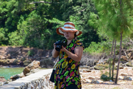 plump: Asia woman plump body in colorful dress with hat check a photo in camera after her take a photo at beach with blue sea when travel