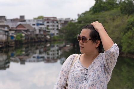 plump: Asia woman plump body with sunglasses standing at river side when travel