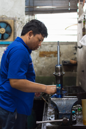 vibration machine: Bangkok, Thailand - May 28, 2016 : Unidentified serviceman checking shock absorber in car suspension at garage Editorial