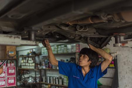disassembly: Bangkok, Thailand - May 28, 2016 : Unidentified serviceman checking a car for fix and repair at garage Editorial