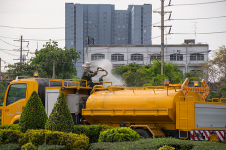 Bangkok, Thailand - May 28, 2016 : Unidentified Bangkok Metropolitan Administration worker working for watering the lawn on road by water tanker truck in Bangkok, Thailand.