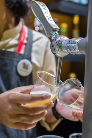 draught: Bangkok, Thailand - May 28, 2016 : Unidentified barman or bartender pouring a draught lager beer from beer tap on counter for serving in a restaurant or pub.