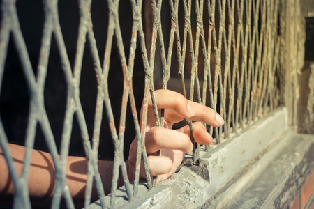 incarcerated: Hands of the woman on a steel lattice close up , process in vintage style Stock Photo