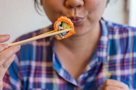 plump: Asia woman plump body holding chopsticks with a california roll in japanese food buffet restaurant. Stock Photo