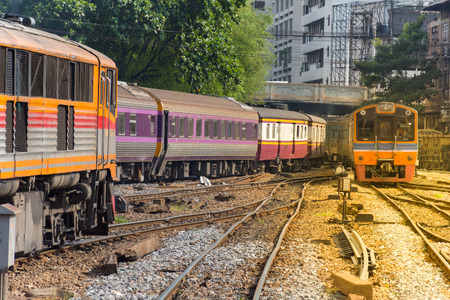Railway train on the railroad tracks in Bangkok station. Many people in Thailand popular travel by train because it is cheaper. , process in soft orange sun light style Stock Photo