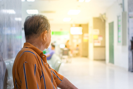 Patient elderly and many patient waiting a doctor and nurse in hospital , process in soft orange sun light style 版權商用圖片