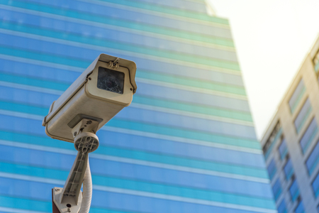 Security camera (CCTV) for safety on blue sky and city background , process in soft orange sun light style Stock Photo