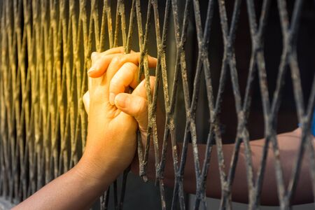 Hands of the man and woman on a steel lattice close up , process in soft orange sun light style
