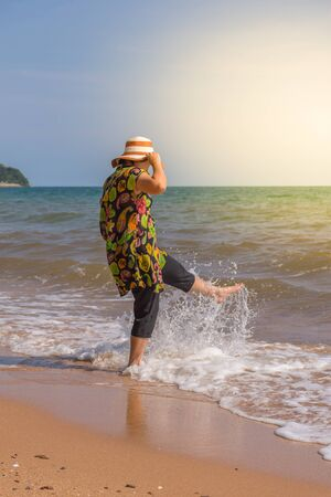 Asia woman plump body in colorful dress with hat posing at beach with blue sea and sky when travel , process in soft orange sun light style Stock Photo
