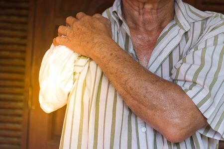 Asia elderly man have tanned skin disabled with one arm and arm prosthetic because accident , process in soft orange sun light style Stock Photo