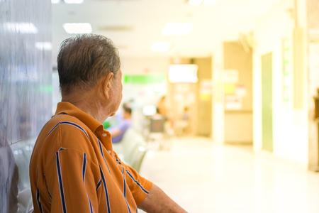 Oudere patiënt en veel geduldig wachten een arts en een verpleegster in het ziekenhuis, proces in zachte oranje zonlichtstijl Stockfoto