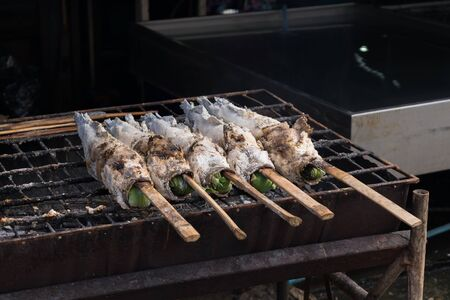 snakehead: Salt-Crusted Grilled Snakehead fish grill on charcoal stove at market Stock Photo